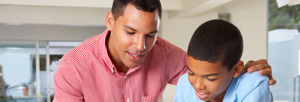 Father assisting his son with his homework.