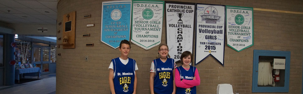 Three St. Monica Catholic School athletes in front of several sports banners on the wall.